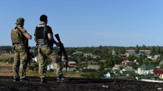Ukrainian loyalist fighters from the Azov Battalion stand guard on a hill on the outskirts of Mariupol on August 30