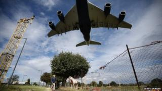 A passenger plane comes into land over a field containing horses at Heathrow Airport