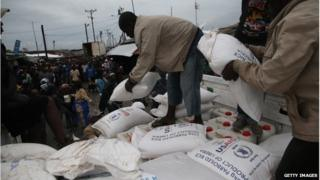 Residents of the West Point slum in Monrovia, Liberia, receive food aid on 21 August 2014.