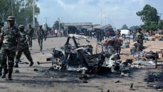Military officers walk past the remains of a car after an explosion on 23 July 2014 in Kaduna, north of Nigeria.
