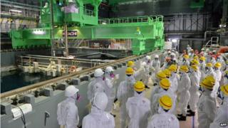 Tepco workers watching an operation to move a spent fuel rod to a cask in the spent fuel pool of the unit four reactor building in 2013