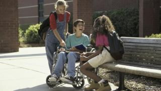 A boy in a wheelchair with two female friends, one of them is sitting on a bench