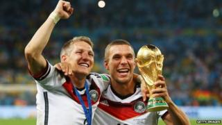 Bastian Schweinsteiger and Lukas Podolski of Germany celebrate with the World Cup trophy after defeating Argentina 1-0 in extra time in the 2014 final