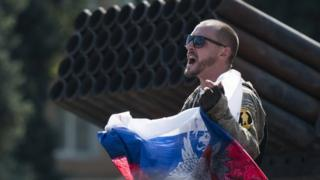A pro-Russian rebel holds a Russian national flag near to damaged heavy hardware from the Ukrainian army during an exhibition in the central square in Donetsk, eastern Ukraine, Sunday, Aug. 24