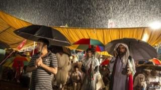Anti-government protesters listen to their leader Tahir ul-Qadri, a Sufi cleric and leader of the Pakistan Awami Tehreek (PAT) political party, during heavy rain in front of the Parliament house in Islamabad, 4 September 2014