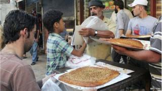 A vendor sells traditional bread during the Muslim holy fasting month of Ramadan in Raqqa province, eastern Syria, which is controlled by the Islamic State, July 23