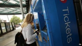 A woman using a train ticket machine