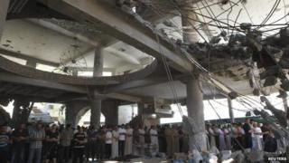 Prayers in the remains of a mosque in Gaza City, 5 Sept