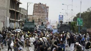 Houthis flee as riot police use tear gas to disperse them along a main road leading to the airport in Sanaa September 7
