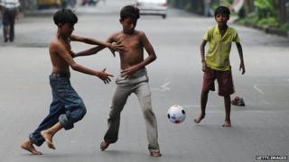 Indian boys play football in a near empty road in Calcutta