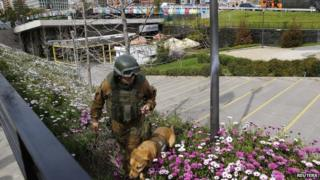 A police dog handler near the area where a bomb exploded in Santiago. 8/9/14