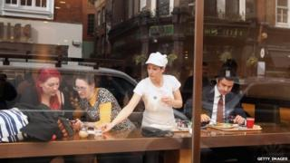 Waitress clearing up at cafe in central London
