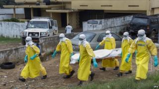 Liberian health care workers on an Ebola burial team collect the body of an Ebola victim at a motor vehicle garage in Paynesville on the outskirts of Monrovia, Liberia (9 September 2014)