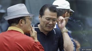 Elderly South Korean job seekers smoke during an elderly persons' job fair on 23 September 2005 in Seoul, South Korea.