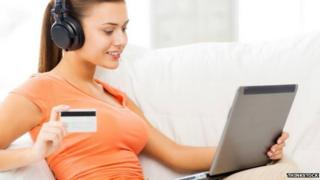Woman listening to music while making online purchase