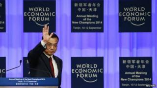Chinese Premier Li Keqiang waves to attendants after making a speech during the World Economic Forum
