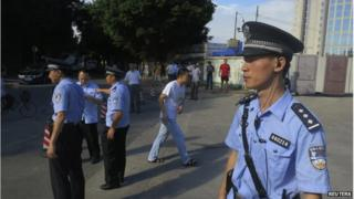 Police officers stand guard outside the court house, blocking roads to the Guangzhou People's Court in the southern Chinese city of Guangzhou 12 September 2014.