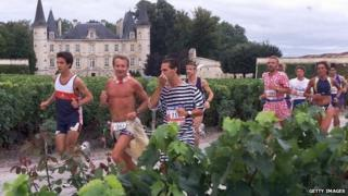Participants run past Chateau Pichon-Longueville and its vineyards by Pauillac
