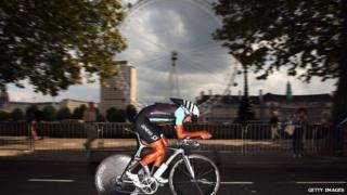 A cyclist in front of the London Eye