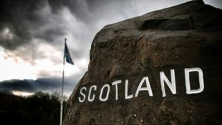 Scotland border sign with flag in background