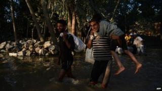 Kashmiri residents wade through floodwaters in Rakshalana, south of Srinagar, on September 15, 2014.