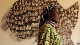 An African refugee walks with her son on 17 June 2013 past a map of Africa at an exhibition hall in Rabat, Morocco
