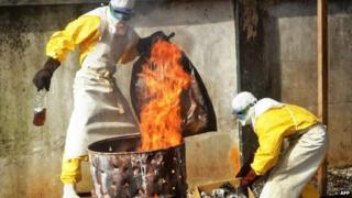 Health workers burn used protection gear at the NGO Medecins Sans Frontieres (Doctors Without Borders) centre in Conakry, Guinea, 13 September 2014