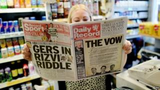 A lady reads The Daily Record in Edinburgh that features a pledge by the leaders of the three main parties in Westminster for more powers in Scotland if it rejects independence