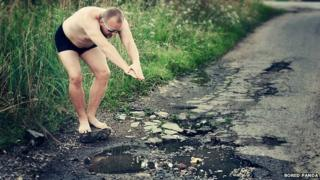 Man pretending to dive in a pothole