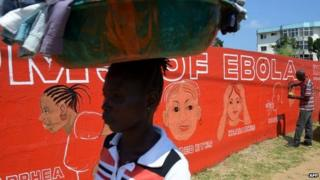 Street artist Stephen Doe paints on 8 September 2014 a mural to inform people about the symptoms of the deadly Ebola virus in Monrovia, Liberia