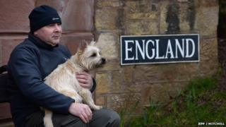 """A man and a dog sit next to a sign saying """"England"""""""