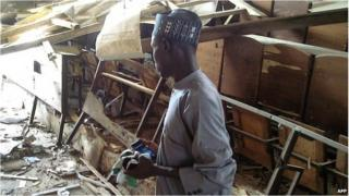 A student looks over at the damage to a lecture hall at the Federal College of Education in the northern Nigerian city of Kano