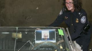 A US Customs and Border Protection official shows the interior of a classic British roadster, a 1967 Jaguar E-Type convertible that was stolen 46 years ago, to Ivan Schneider by video link