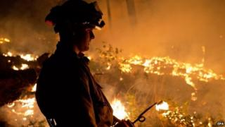 A firefighter uses a drip torch to set a controlled burn around the King Fire which burns near the town of Pollock Pines, California, US, 17 September 2014