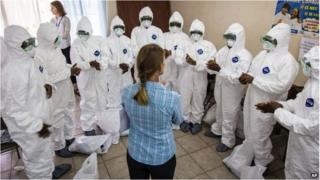 A World Health Organization worker trains nurses to use Ebola protective gear in Freetown, Sierra Leone