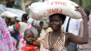 A woman with a child carrying a sack of rice