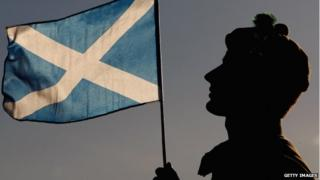 A highlander hold up a Scottish Saltire flag