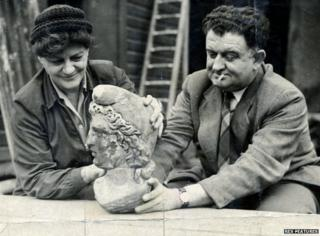 Two people holding up the newly discovered head of Mithras, 1954