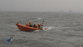 A lifeboat crew approaches the sunken boat
