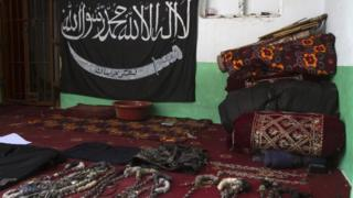 A black Jihad flag, handcuffs and chains are displayed in a house used by Taliban militants as a prison after a military operation against the militants in the town of Miranshah in North Waziristan July 9, 2014