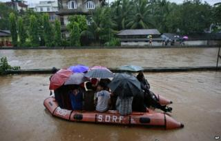 State Disaster Response Force personnel rescue people on a boat in a flooded area during heavy monsoon rains in Gauhati, Assam state, India, Monday, Sept. 22, 2014.
