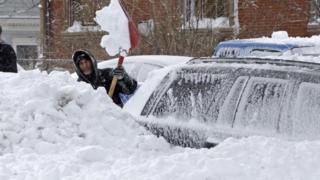 man shovelling his car out of deep snow