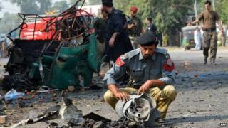 Pakistani police officials examine mangled wreckage at the site of a suicide bomb attack in Peshawar on September 23, 2014.