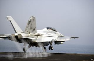 A US warplane launches from the flight deck of the aircraft carrier USS George HW Bush in the Gulf, 15 August