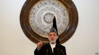 Outgoing Afghan President Hamid Karzai gestures as he addresses a gathering of government employees at the Presidential Palace in Kabul on September 23, 2014.