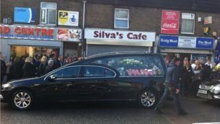 Funeral cortege outside Silva's Cafe