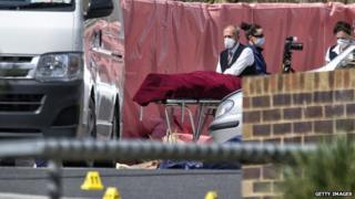 The body of Abdul Numan Haider is removed from the scene of the incident in Endeavour Hills on 24 September 2014 in Melbourne, Australia