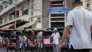 A group of cyclo drivers wait for customers in front of one of the street markets in the city centre on 13 August 2014 in Phnom Penh, Cambodia.