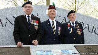 Normandy veterans in front of memorial