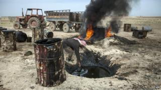 A man works at a makeshift, or teapot, oil refinery in Syria's Raqqa province (15 April 2013)